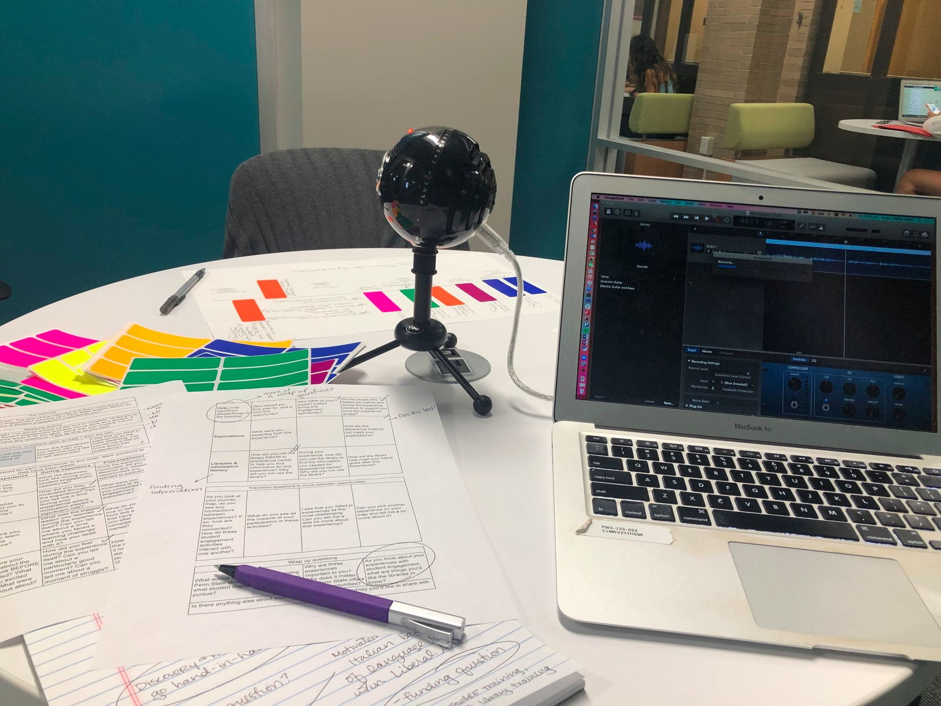 A picture of a table with a laptop, snowball microphone, and paper