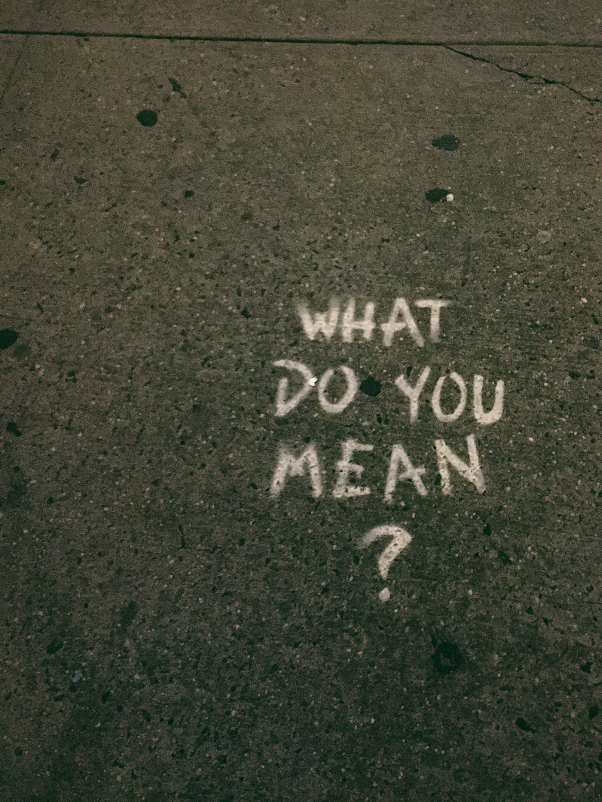 """A sidewalk with the words """"What do you mean?"""" written on the ground"""